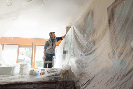 House painter painting the interior of a furnished house Zdjęcie Seryjne