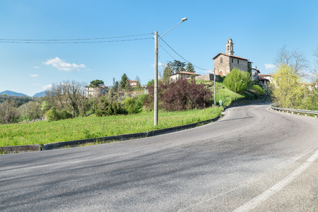 Malnate, province of Varese, Italy. Street at the entrance of the town of Malnate with the church of San Matteo. The church dates back to the 11th century with modifications up to the 18th century