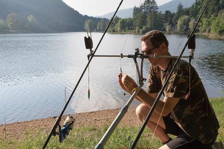 Fishing adventures, carp fishing. Angler is preparing the equipment