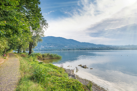 Lake Varese, summer landscape, Italy. Cycle - pedestrian track that runs along all the lake near Biandronno village. In the background the mountain called Campo dei Fiori is visible