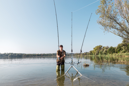 Fishing adventures, carp fishing. Fisherman with green rubber boots and camouflage clothing is in the water with a fishing rod in hand. Front view and copy space