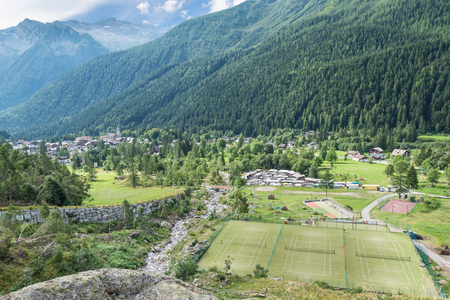 Macugnaga, Italy. Mountain village in the Alps at the foot of Monte Rosa with some recreational facilities in the foreground, tennis, basketball and bowling courts. At the center, the weekly market Zdjęcie Seryjne