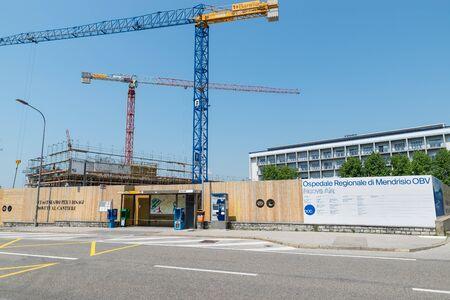 Mendrisio, Switzerland  – June 4, 2019: Mendrisio Regional Hospital (OBV), new wing construction work (as written on white billboard). Work on widening the hospital called Beata Vergine Zdjęcie Seryjne