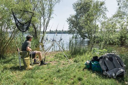 Fishing adventures, carp fishing. Sport and technology. Angler with modern and technological equipment for sport fishing Zdjęcie Seryjne