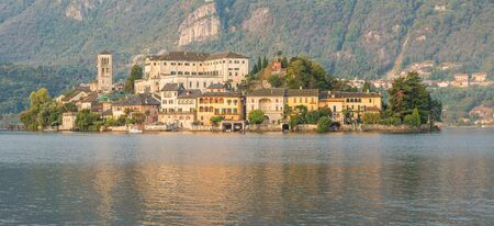 Lake with picturesque island. Lake Orta and the island of San Giulio at sunrise. Famous tourist place and large lake in northern Italy