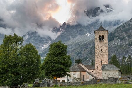 Picturesque old mountain church at sunset. Traditional alpine village, Macugnaga with in the background the Monte Rosa , Piedmont, Italy Zdjęcie Seryjne
