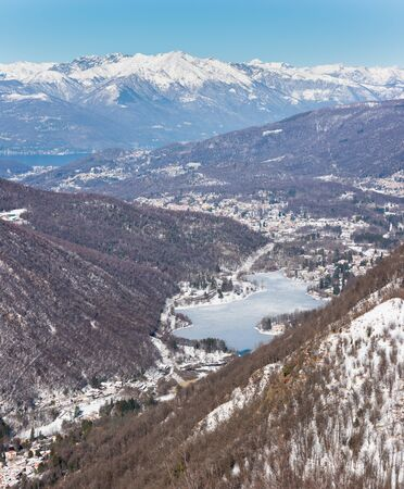 Northern Italy in winter. Aerial view from Valganna with Lake Ghirla to Lake Maggiore with Luino. In the background the Alps. The villages of Ganna, Ghirla, Cunardo, Germignaga - Luino are visible