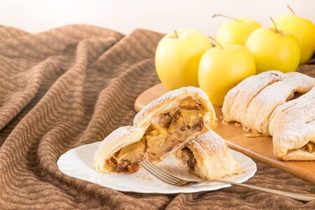 Slice of homemade apple strudel (apples pie) with puff pastry, cinnamon and raisin