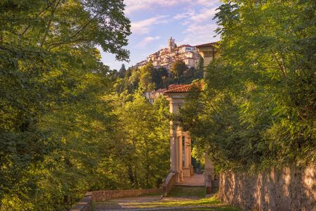 Old and famous Italian medieval village. Sacro Monte of Varese with the holy road that leads to medieval village (in the background), with the eleventh chapel. World Heritage Site – Unesco Banco de Imagens - 127529115