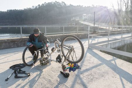 Man cyclist repairs a bicycle with flat tire during a trip. Concept of unforeseen and bad luck