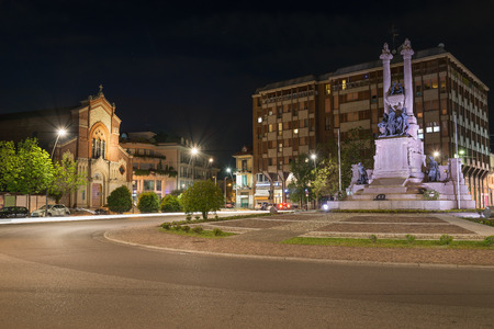 Italian city at night, art and culture. Gallarate, square Risorgimento with monument to the fallen for the homeland of the war of 1915 – 1918 (first and second world war) and church of San Francesco
