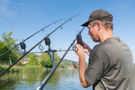 Fishing adventures, carp fishing. Angler is preparing the equipment. Outdoor recreation concept Reklamní fotografie