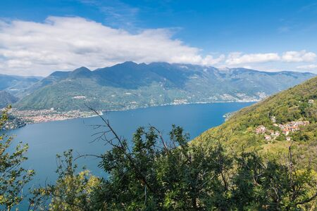 Big european lake in the mountains seen from above. Lake Maggiore, Italy, with the city of Cannobbio on the left. Amazing summer landscape