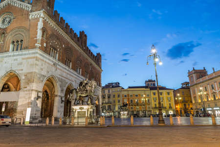 Medieval city at dusk. Piacenza, historic center, Italy. Piazza Cavalli (Square horses) with palazzo Gotico (Gothic palace - XIII century) and Governor's palace on the right, Emilia Romagna