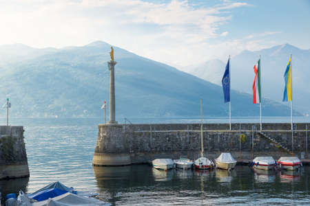 Small and characteristic harbor on the lake with boats and sun rays filtering from the clouds in the background. Tourism concept. Lakefront Luino on Lake Maggiore, Italy Redakční