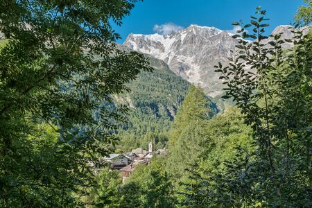 Mountain in summer. Stunning view of a village in the Italian Alps. Macugnaga and the majestic Monte Rosa, Anzasca valley, Piedmont. Important summer and winter resort in northern Italy
