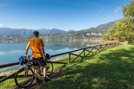 Stunning italian lake. Lake Pusiano with in the background the town of Pusiano view from Bosisio Parini lake front. Tourist man with bicycle on lake observes the panorama