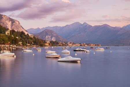 Lake Maggiore at sunrise, Italy. Panorama from the lakefront of the town of Stresa towards Baveno with boats and silk water effect Reklamní fotografie