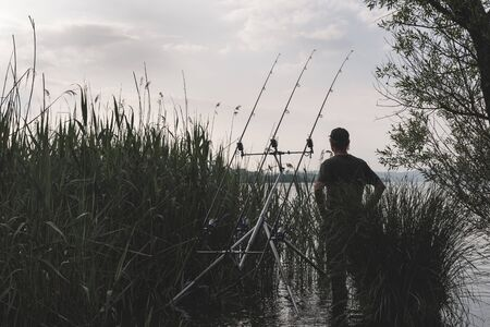 Fishing adventures, carp fishing. Man fishing on lake. Concept of patience, waiting, relaxation and healthy lifestyle in the nature. Moody look
