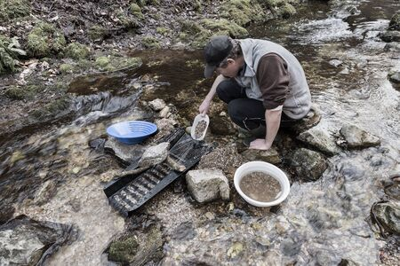 Outdoor adventures on river. Gold panning, man pours sand and gravel into a sluice box in search of gold Reklamní fotografie