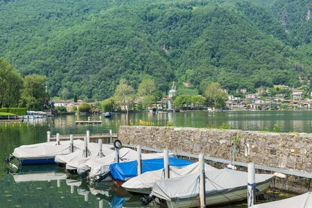 Small Swiss harbor on Lake. Canton Ticino with Lake Lugano and the town of Riva San Vitale in the background, Switzerland, at the foot of Monte San Giorgio UNESCO site for fossiliferous deposits