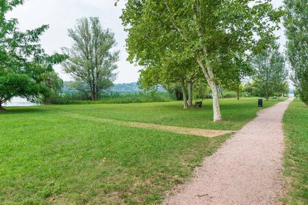 Dirt path in the park by the lake, Lake Varese and the green area of Schiranna or Zanzi park, northern Italy. Lake famous because hosts rowing competitions of national, European and world level