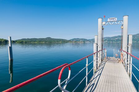 Modern steel pier on the lake for tourist boats. Lake Maggiore at the lakefront of the town of Ispra, northern Italy, with on the left the park of the Golfo della Quassa