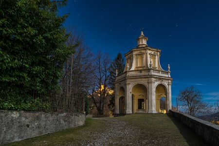 Sacred way in the moonlight. Sacro Monte di Varese, Italy,   with the thirteenth chapel and the village of Sacro Monte illuminated on the left in the distance