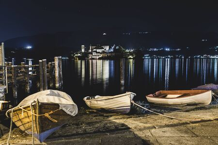 Night lake with boats. Lake Orta at the picturesque village of Orta San Giulio (square Motta) with the illuminated island of San Giulio in the center, northern Italy