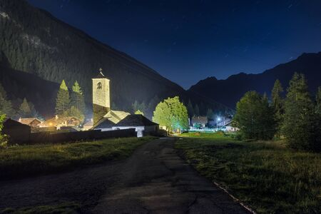 Old mountain church at night. Traditional alpine village, Macugnaga, Italy, with the old church and the secular linden tree (XIII century) on the right, important symbol for the local community Reklamní fotografie