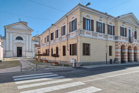 Small Italian town with the town hall and the church. Casalbeltrame town, street Vittorio Emanuele and the parish of Santa Maria Assunta (18th century). Piedmont region
