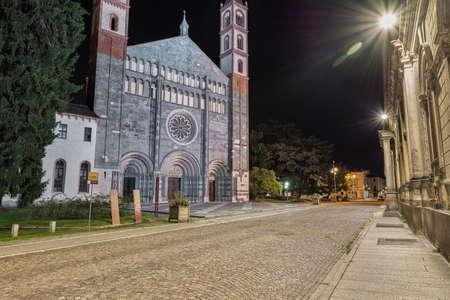 Gorgeous abbey at night. Vercelli city, Italy. Abbey or basilica of Sant'Andrea, XIII century, street Francigena as written on the yellow and brown sign on the left. Stage of the famous Via Francigena