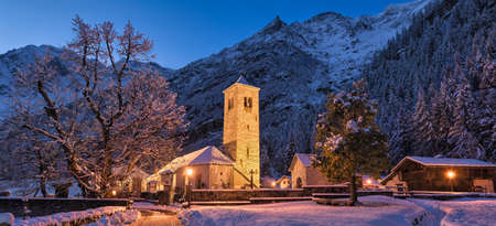 Winter night panorama with snow and an old illuminated church and mountains as a background. Macugnaga village, Anzasca valley Italy, an important tourist resort in the european Alps 版權商用圖片
