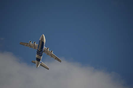 Blue and White Commercial Airplane Flying Upwards Stock Photo