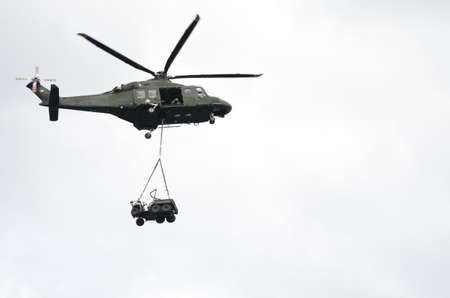 hover: Green Military Helicopter Carrying a Jeep