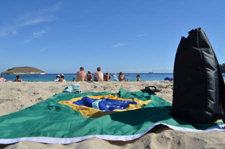 Outstretched Flag of Brazil and a Black Backpack on the sand of Barceloneta Beach in Barcelona, Spain Editöryel