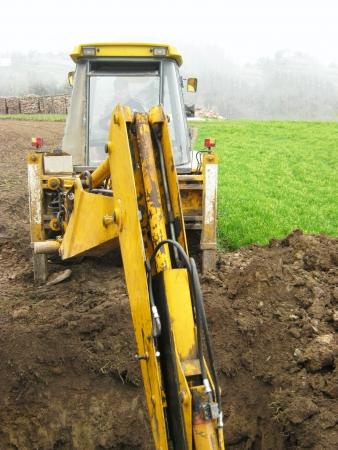 Big yellow excavator on construction site photo