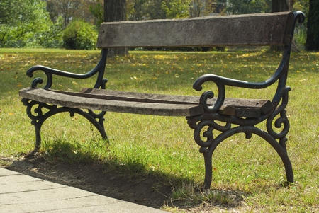 Wooden and metal bench in park at beautiful sunny day Zdjęcie Seryjne