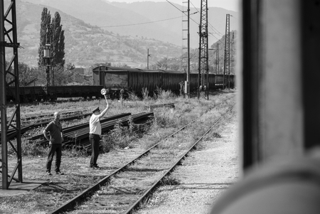 Dispatcher at the train station giving signal to the train Editorial