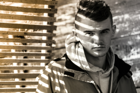 film noir: Young man posing in red jacket covered with beautiful film noir style shadow at sunny day autumn fall season