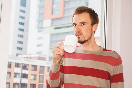handsom: Handsom man standing by the window having coffee at home in the living room Stock Photo