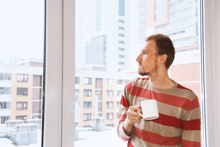 handsom: Handsom man standing by the window having coffee and looking on the citiy