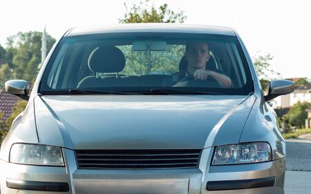 moder: Young adult modern dressed sitting in moder car  and prepearing to star engine Stock Photo