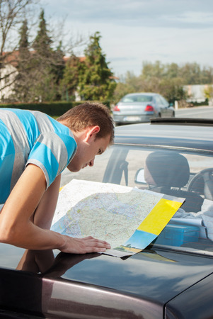 bended: Traveler searching the routes on the map bended to car Stock Photo