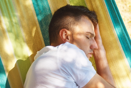 enyoing: Young man laying on hanging chair and enyoing sunlight Stock Photo