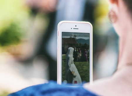 over the shoulder: Woman taking picture with modern smartphone. Over shoulder view.