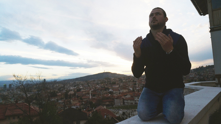 Young adult man praying outdoor with hands up in the air dua pose