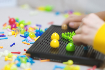 Child playing creative pin board game with colorful plasitc peaces