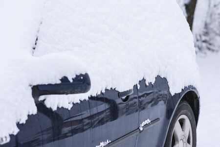 Side view of car under the snow texture at cold winter snowy day.