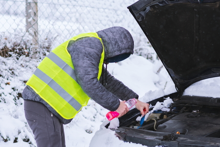 Man dressed in neon green vest pouring antifreeze coolant to car engine at cold winter day. Archivio Fotografico